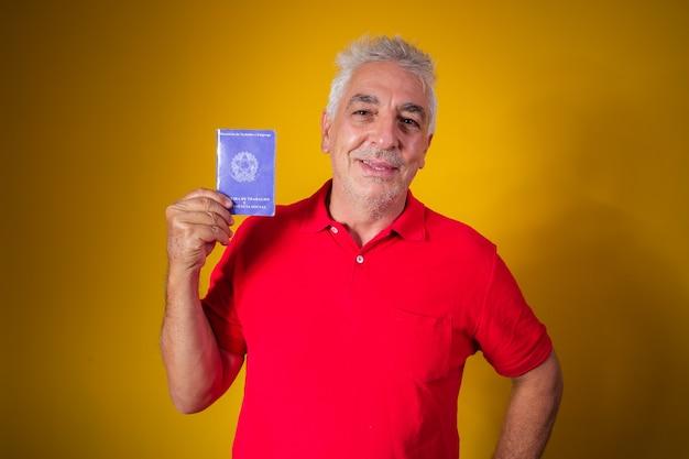 Älterer mann mit einer brasilianischen arbeitskarte holding