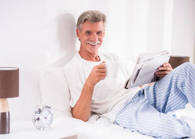 Älterer mann mit einer tasse kaffee liest zeitung im bett.