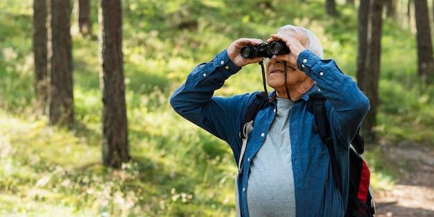 Älterer mann mit fernglas beim erkunden der natur