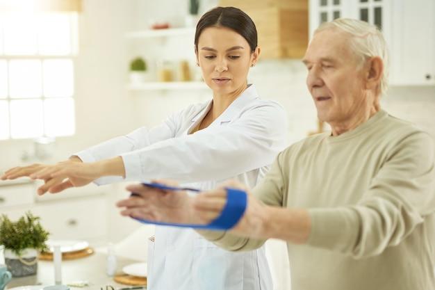 Älterer mann mit fitness-gummiband in den händen während der rehabilitation