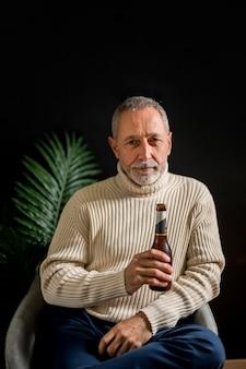 Älterer mann mit flasche bier