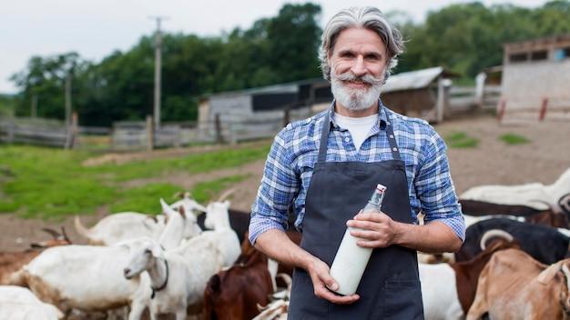 Älterer mann mit flasche ziegenmilch
