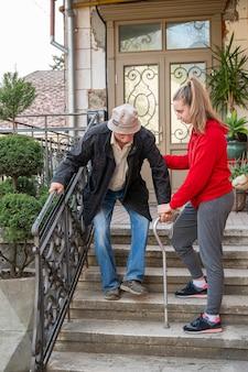 Älterer mann mit gehstock, der mit enkelin im freien geht