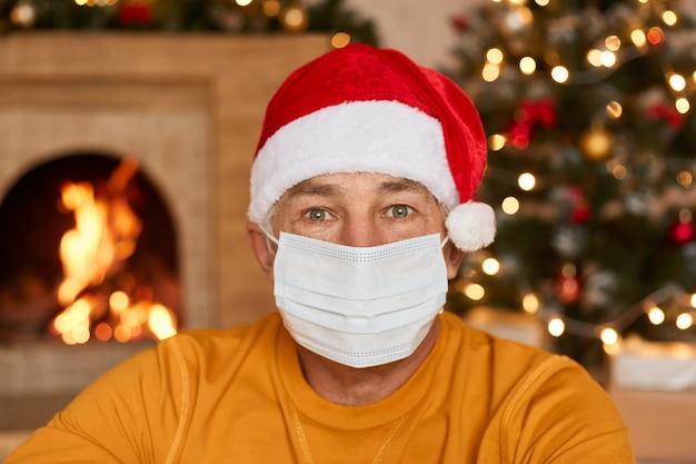 Älterer mann mit gekleidet in einer schutzmaske auf seinem gesicht und weihnachtsmütze betrachtet kamera, die in festlichem raum mit unscharfem kamin und weihnachtsbaum aufwirft. bleib zuhause.