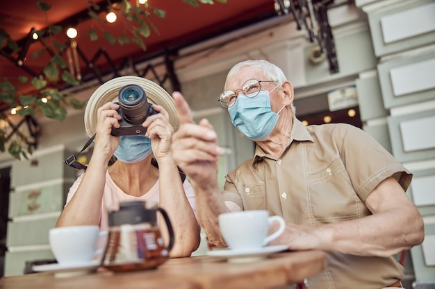 Älterer mann mit gesichtsmaske, der auf etwas in der ferne zu einer fotografin zeigt
