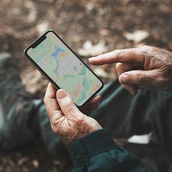 Älterer mann mit gps-navigation auf seinem smartphone