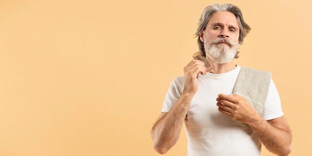 Älterer mann mit handtuch, das seinen bart kämmt