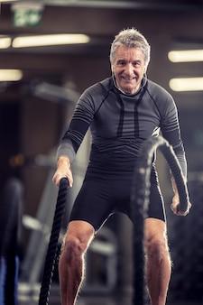 Älterer mann mit kopfhörern trainiert mit seilen in einem fitness-trainingszentrum.