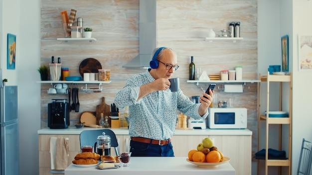Älterer mann mit kopfhörern, während er morgens beim frühstück musik hört. älterer rentner, der einen modernen, fröhlichen lebensstil genießt, entspannt tanzt, lächelt und moderne technologie verwendet