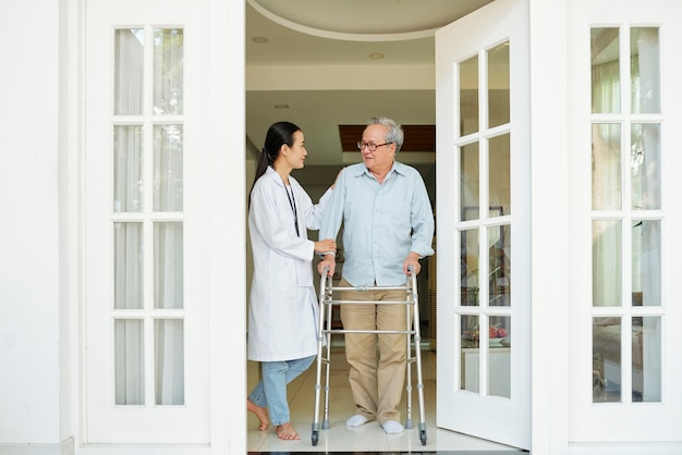Älterer mann mit krankenschwester wird gehen
