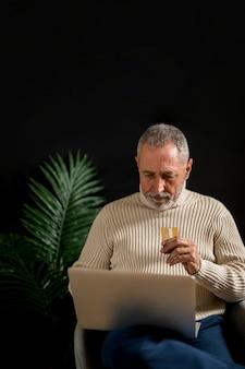 Älterer mann mit kreditkarte unter verwendung des laptops
