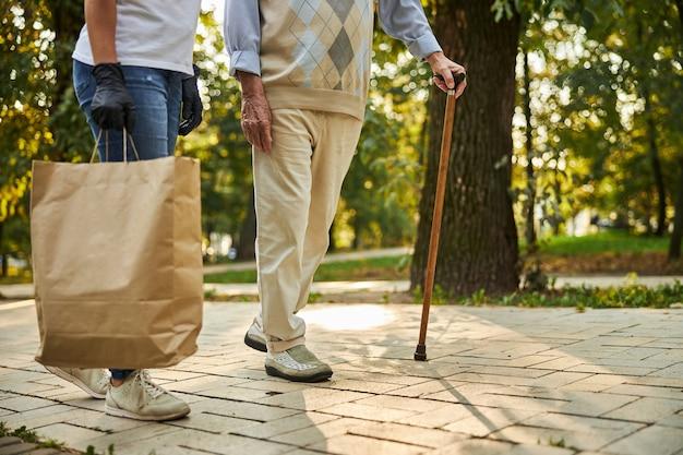 Älterer mann mit krücke und weiblicher kaufhilfe