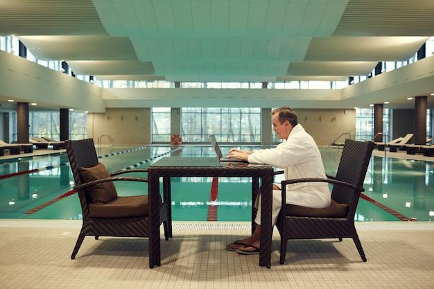 Älterer mann mit laptop im spa resort