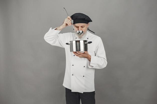 Älterer mann mit metallpfanne. koch in einem schwarzen hut. professionelle herangehensweise an das geschäft.