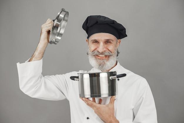 Älterer mann mit metallpfanne. koch in einem schwarzen hut.