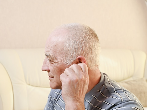 Älterer mann mit ohrenschmerzen.