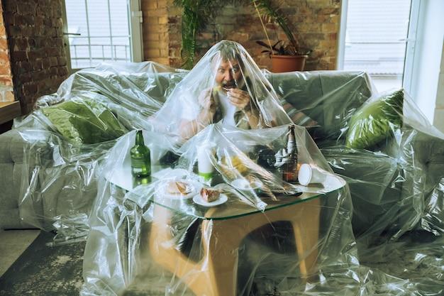 Älterer mann mit plastik bedeckt, der fast food isst und bier trinkt umweltverschmutzung durch menschen