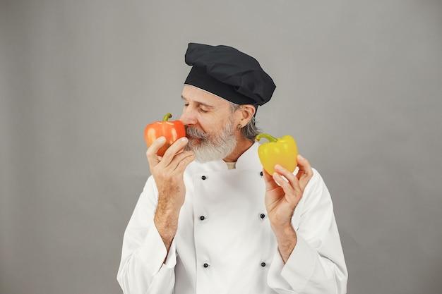 Älterer mann mit rotem und gelbem peper. professionelle herangehensweise an das geschäft.