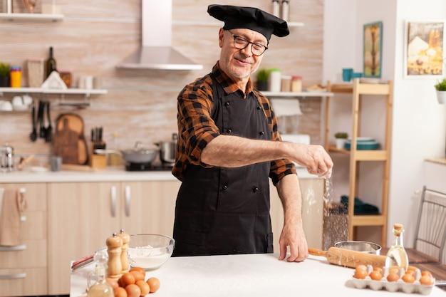 Älterer mann mit schürze lächelnd, während er das mehl mit der hand auf den küchentisch streut?