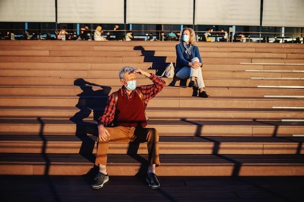Älterer mann mit schutzmaske beim draußen sitzen auf der treppe und auf der suche nach seinem freund.