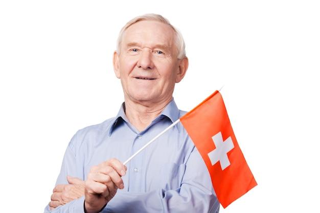Älterer mann mit schweizer flagge. fröhlicher älterer mann, der die flagge der schweiz hält und in die kamera lächelt, während er vor weißem hintergrund steht