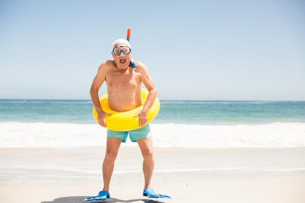 Älterer mann mit schwimmring und flossen am strand