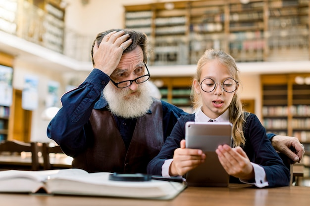 Älterer mann mit seiner enkelin benutzt ein digitales tablet in der bibliothek. mädchen liest informationen von tablette, und großvater ist verwirrt und überrascht