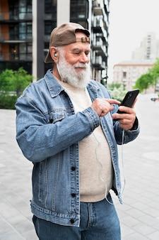 Älterer mann mit smartphone draußen in der stadt