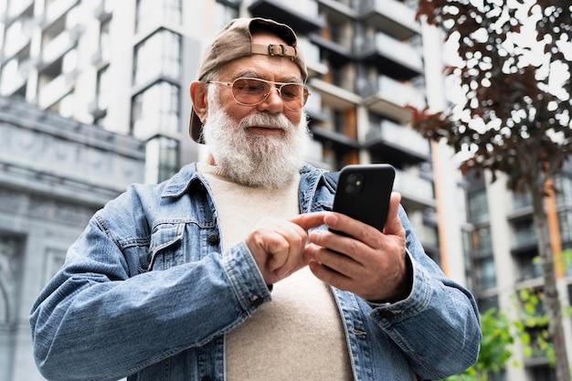 Älterer mann mit smartphone im freien in der stadt