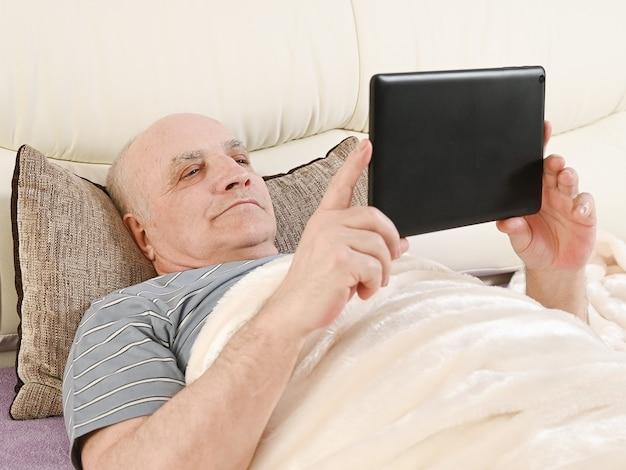 Älterer mann mit tablette auf bett.