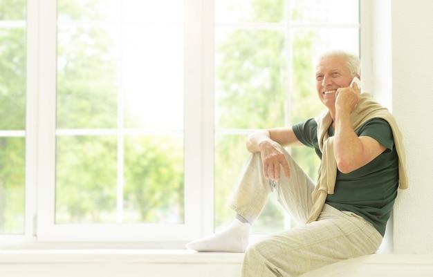 Älterer mann mit telefon, der zu hause auf der fensterbank sitzt