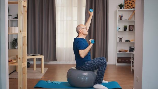 Älterer mann mit vitalitätstraining mit hanteln im wohnzimmer. alten rentner gesundes training gesundheitssport zu hause, fitness-aktivität im alter ausüben