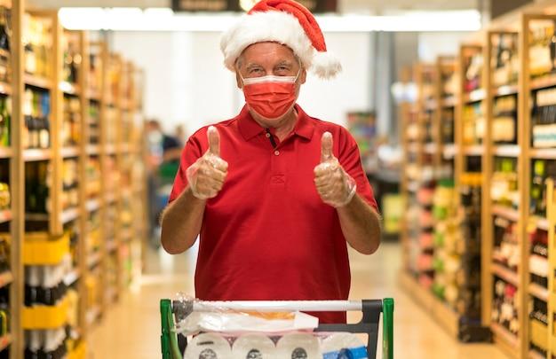 Älterer mann mit weihnachtsmütze, der eine schützende gesichtsmaske trägt, die den wagen im supermarkt schiebt