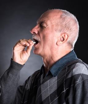 Älterer mann möchte eine pille auf dunklem hintergrund nehmen
