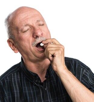 Älterer mann möchte eine pille auf weißem hintergrund nehmen