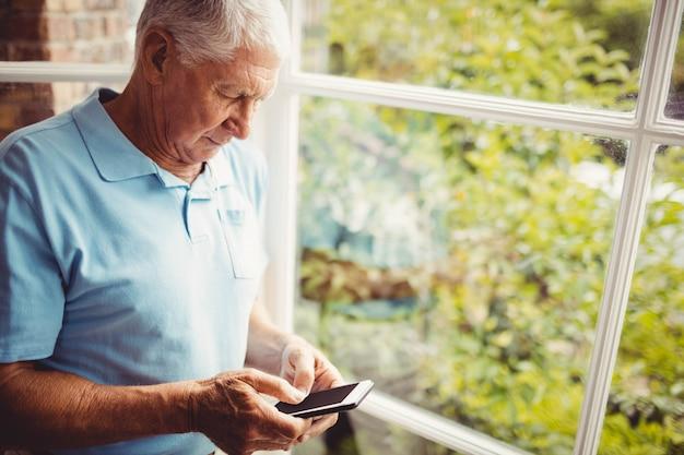 Älterer mann nahe bei dem fenster unter verwendung des smartphone zu hause