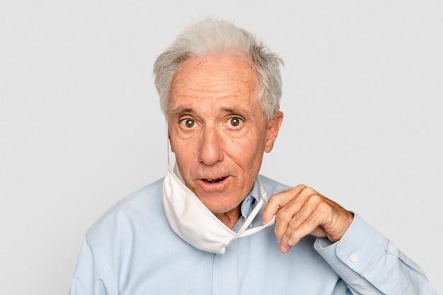 Älterer mann nimmt maske in der neuen normalität ab