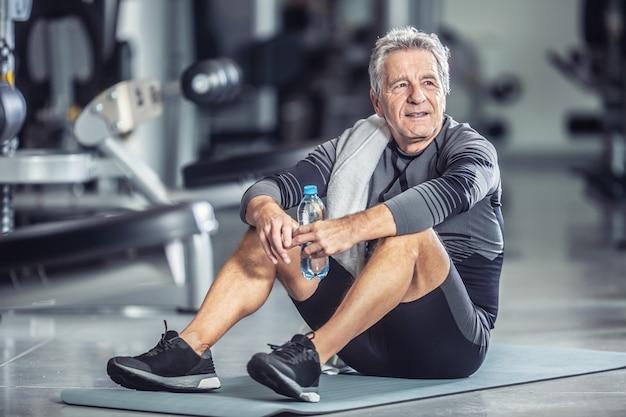 Älterer mann ruht mit einer flasche wasser auf einer matte während eines fitnesstrainings.