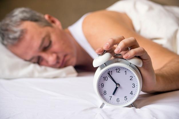 Älterer mann schläft im bett mit wecker im vordergrund im schlafzimmer. erschöpfter mann wird durch einen wecker in seinem schlafzimmer geweckt. wakeed up