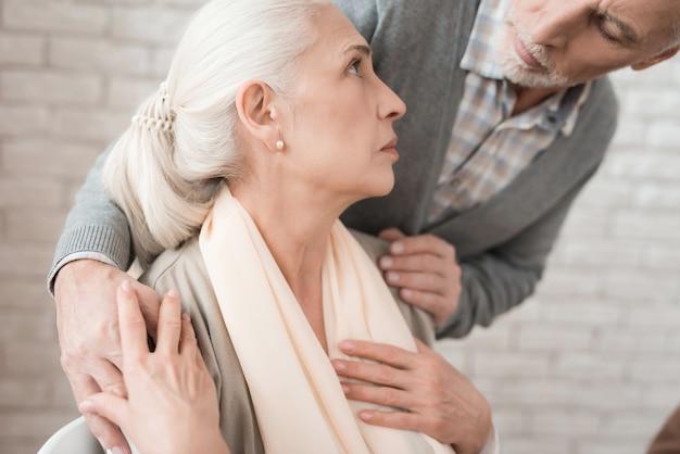 Älterer mann sorgt sich um frau, die herzschmerz hat.