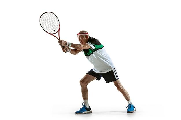 Älterer mann spielt tennis in sportkleidung isoliert auf weißer wand