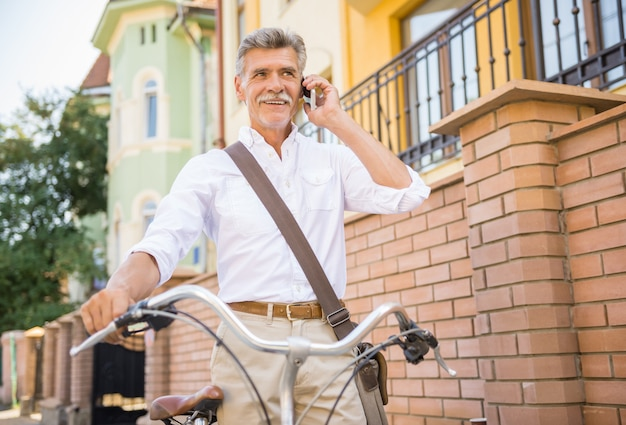 Älterer mann spricht durch das telefon, das mit fahrrad steht.
