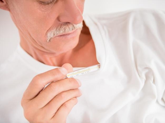 Älterer mann überprüft eine temperatur mit thermometer.