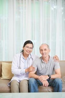 Älterer mann und doktor, die auf sofa im wohnzimmer sitzt