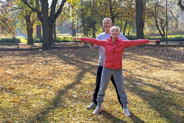 Älterer mann und eine frau, die im herbst zusammen im park trainieren