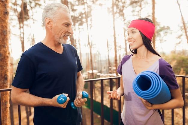 Älterer mann und fitnesstrainer sprechen