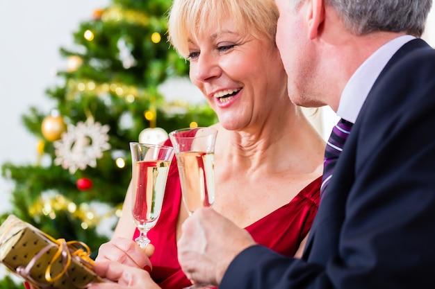 Älterer mann und frau, die heiligabend mit einem glas sekt feiern