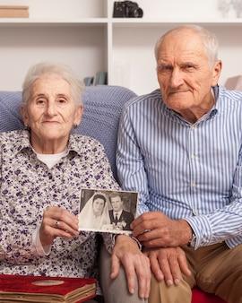 Älterer mann und frau, die hochzeitsbild hält