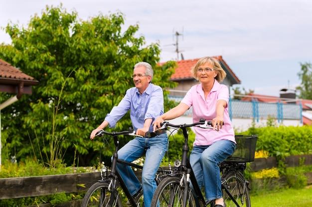 Älterer mann und frau, die mit fahrrädern im freien trainieren, sind ein paar