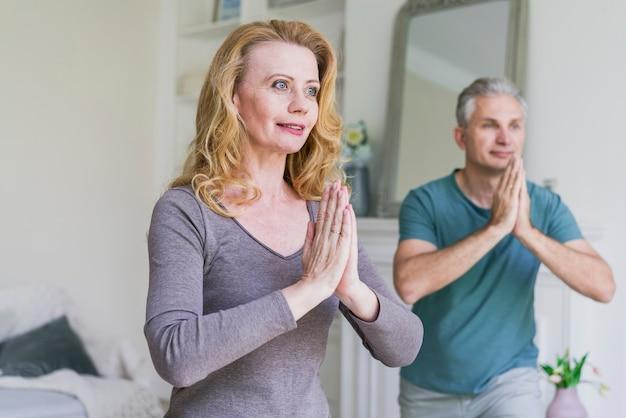 Älterer mann und frau, die zu hause yoga tut